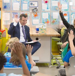 Governor Newsom raises his right hand while reading to children