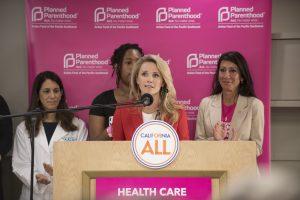 First Partner Jennifer Seibel Newsom speaks at the podium with several women behind her.