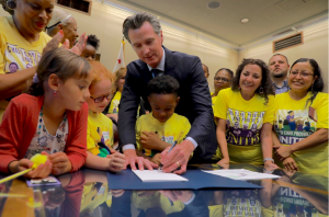 Surrounded by children, Governor Newsom signs child care worker legislation.