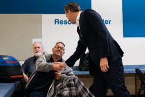 Governor Newsom shakes hands with an individual at the center in Riverside.