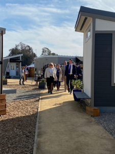 Governor Newsom walks with a tour of people as he visits tiny cabins at the Bridge Housing Community site in San Jose.