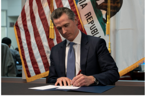 Governor Newsom sits at his desk and signs emergency legislation to fight COVID-19.