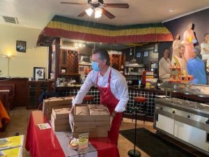 Governor Newsom places a stack of boxed meals onto a red table.