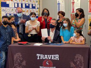 Governor Newsom signs legislation next to students