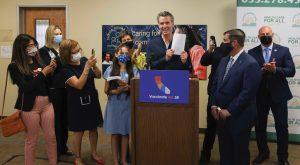 Governor Newsom holds up health trailer bill at signing ceremony
