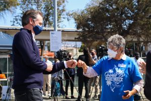 Governor Newsom fist bumps vaccination worker
